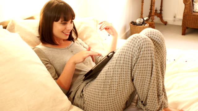 woman in pyjamas using a digital tablet on the bed - double bed stock videos & royalty-free footage