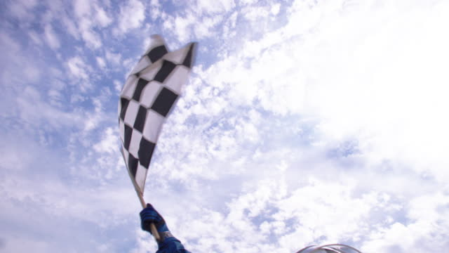 slo mo. woman in racing helmet waves checkered flag in triumph as pit crew lifts her up and cheers. - 旗点の映像素材/bロール