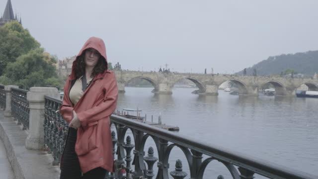 woman in raincoat admires prague on gloomy day - osteuropäische kultur stock-videos und b-roll-filmmaterial