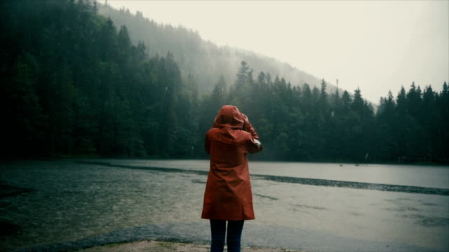 woman in raincoat standing near the lake under the pouring rain - lake stock videos & royalty-free footage