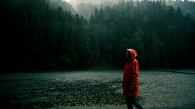 vídeos de stock e filmes b-roll de woman in raincoat standing near the lake under the pouring rain - chuva