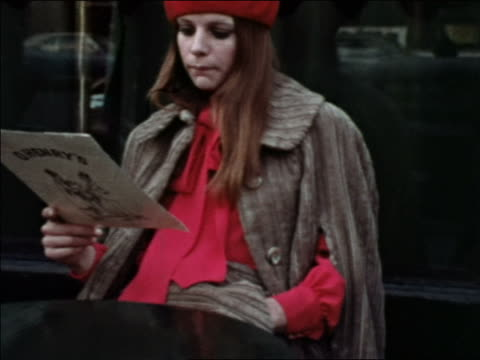 1969 woman in red beret reading menu at sidewalk cafe / zoom in to close up of corduroy cape / NYC