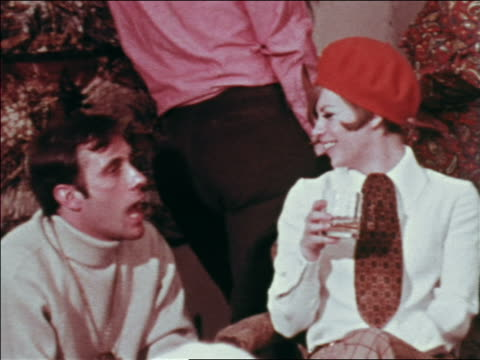 vídeos de stock, filmes e b-roll de 1969 woman in red beret + tie holding beverage talking to man at party / greenwich village, nyc - boina