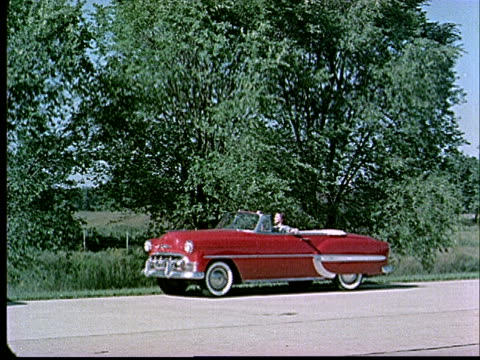 vídeos y material grabado en eventos de stock de 1952 montage ws woman in red convertible car signaling with her arm and pulling onto road / cu woman's gloved hand turning steering wheel / usa - 1952
