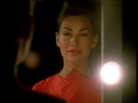 woman in red dress applies perfume in front of mirror - spraying stock videos and b-roll footage