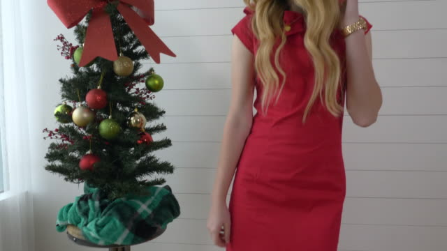 vidéos et rushes de woman in red dress posing next to small christmas tree - robe rouge