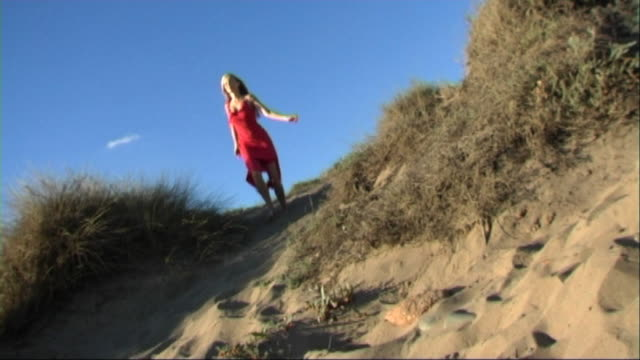 vidéos et rushes de woman in red dress running down sand dune to the sea - robe rouge