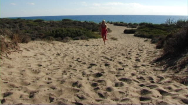 vidéos et rushes de woman in red dress running on beach - robe rouge