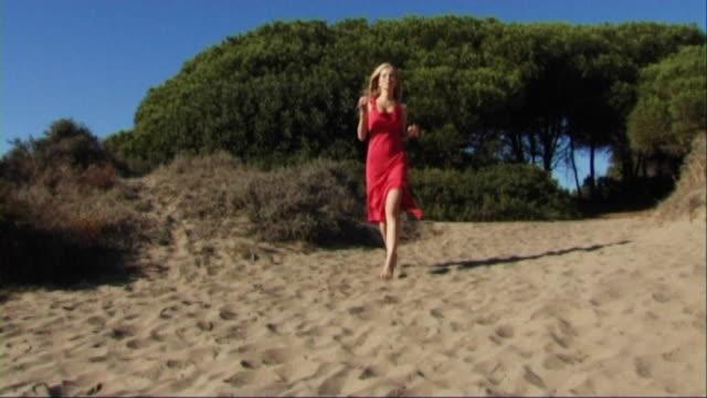 vidéos et rushes de woman in red dress running through sand dunes on beach - robe rouge