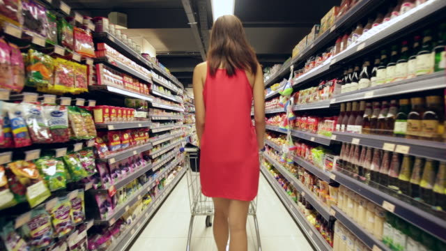 stockvideo's en b-roll-footage met ts rv ms woman in red dress shopping in a grocery store. - shelf