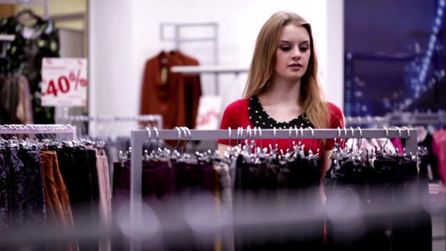 stockvideo's en b-roll-footage met woman in red dress shopping in clothing store - kledinghanger