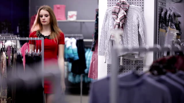 woman in red dress shopping in clothing store - red dress stock videos & royalty-free footage