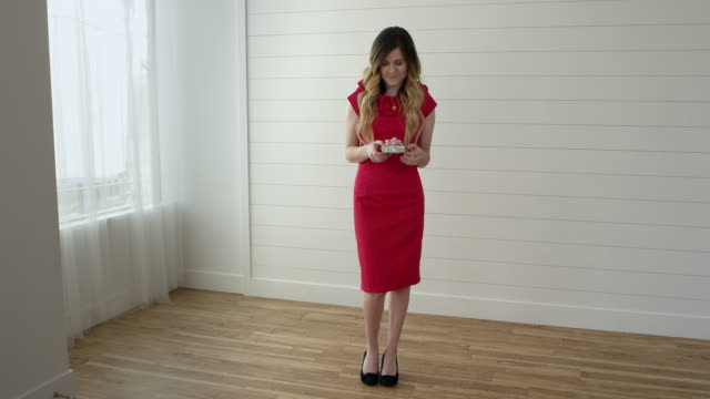 vidéos et rushes de woman in red dress standing in front of window holding gift - robe rouge