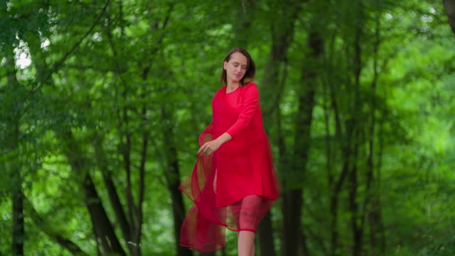 Woman in red dress Twirling in forest