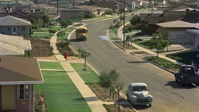 1955 ha ws woman in red dress walking down surburban sidewalk / los angeles, united states - 1950点の映像素材/bロール