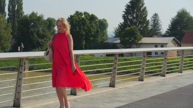 woman in red dress walking in city centre - red dress stock videos & royalty-free footage