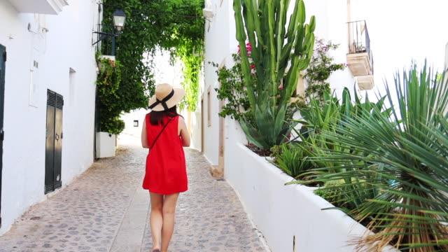 woman in red dress walking in the old city of the ibiza town with summer style and white houses. mujer con vestido rojo en la parte antigua del pueblo de ibiza con casas blancas. - narrow stock videos & royalty-free footage