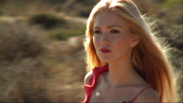 vidéos et rushes de woman in red dress walking through sand dunes on beach - robe rouge