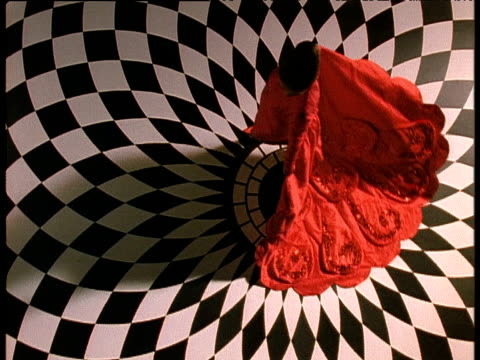 Woman in red dress walks on black and white tiled floor