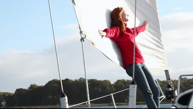 stockvideo's en b-roll-footage met ws woman in red jacket laying back against sail on moving sailboat / copenhagen, denmark - jachtvaren