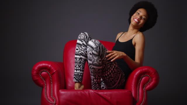 vídeos y material grabado en eventos de stock de  woman in red leather arm chair kicking legs playfully - camisola