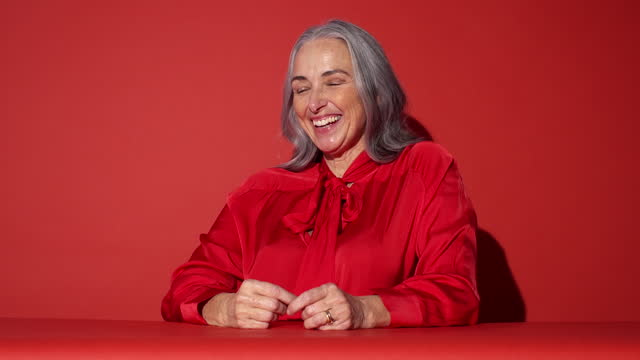 a woman in red poses and looks to camera 2 - grey hair stock videos & royalty-free footage