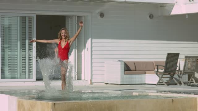 stockvideo's en b-roll-footage met woman in red swimsuit kicks water - tuindeur