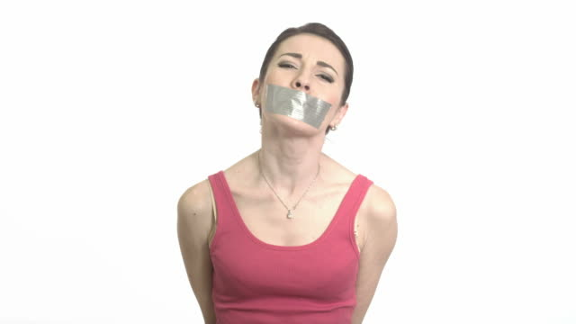 woman in red with gaffer tape on her mouth - trafficking stock videos and b-roll footage