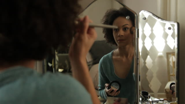 Woman in reflection applying eye lash mascara in front of vanity mirror in tastefully decorated brownstone