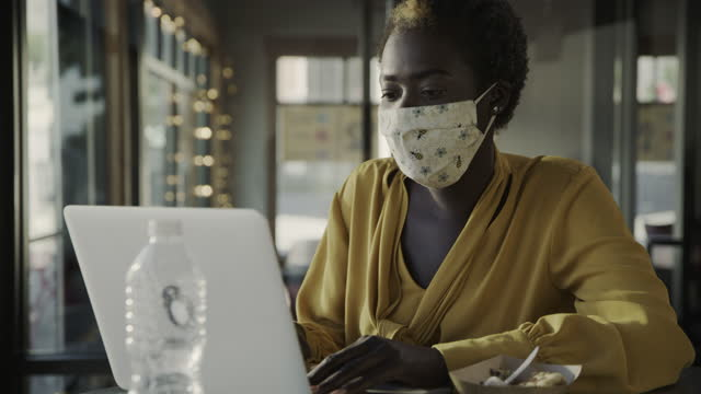 woman in restaurant wearing face mask using laptop during working lunch / pleasant grove, utah, united states - convenience stock videos & royalty-free footage