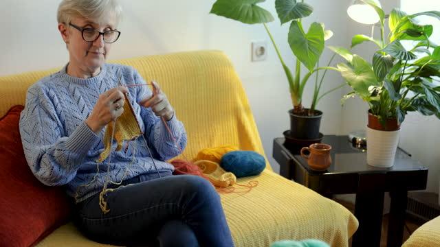 vídeos y material grabado en eventos de stock de mujer en retiro tejiendo un swatter en su sala de estar - tejer