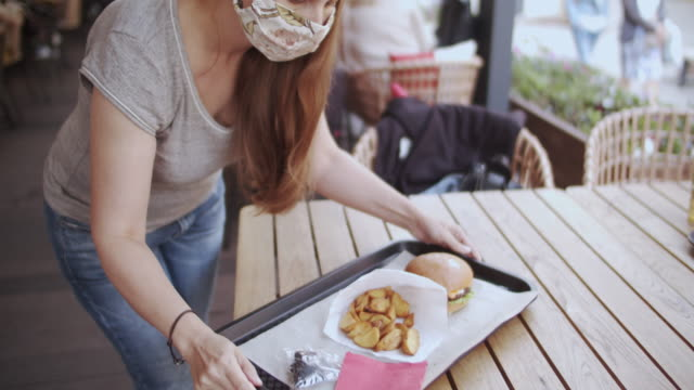 vídeos de stock e filmes b-roll de woman in reusable protective face  mask carrying tray with burger and french fries from a food-court or in a cafe - servir comida e bebida