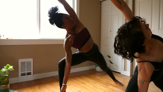 ms woman in revolved side angle pose while practicing yoga with friend in home - yoga stock videos & royalty-free footage