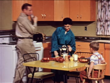 1957 woman in robe bringing coffee pot to kitchen table + pouring milk / man kissing her on cheek - archivmaterial stock-videos und b-roll-filmmaterial