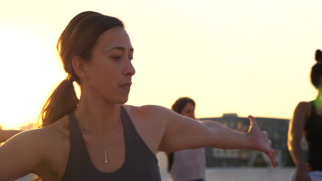 ms woman in rooftop yoga class with friends at sunset - sportbehå bildbanksvideor och videomaterial från bakom kulisserna