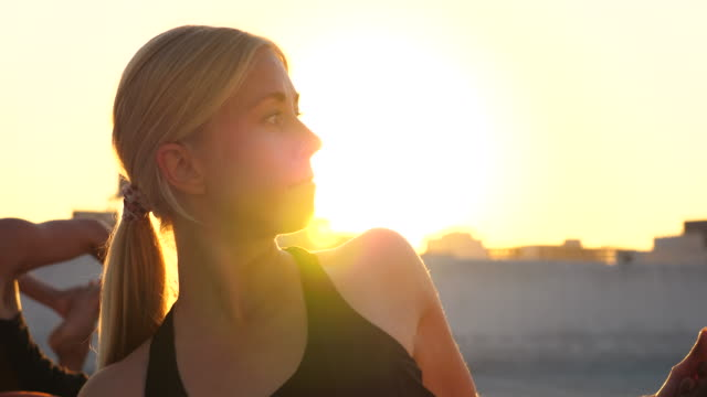 ms woman in rooftop yoga class with friends at sunset - yoga stock videos & royalty-free footage