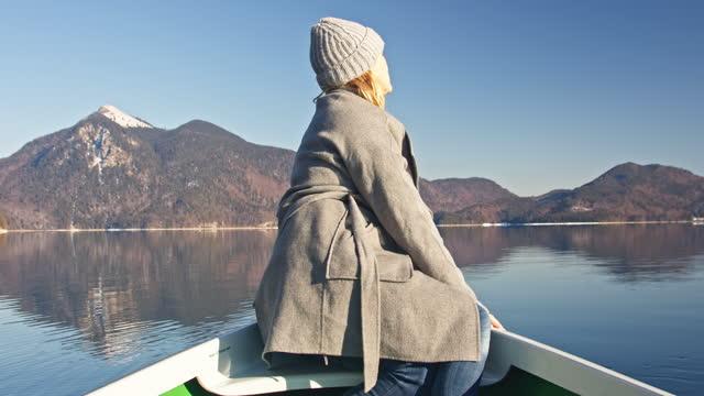 vidéos et rushes de woman in rowing boat on lake enjoying the sunlight - manteau et blouson d'hiver