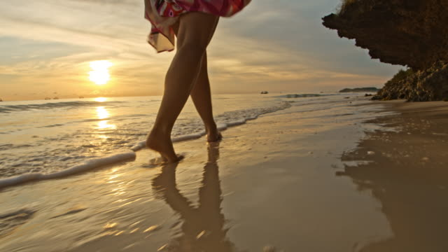la woman in sarong walking on a beach at sunset - low tide stock videos & royalty-free footage
