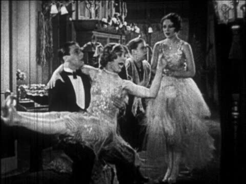 vídeos de stock e filmes b-roll de b/w 1926 woman in sequined dress jumping into man's arms + kissing him / newsreel - 1920