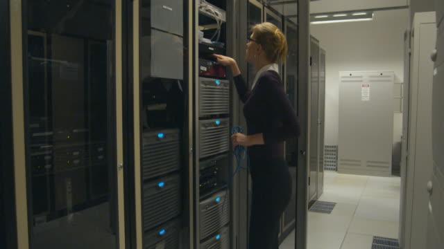 MS Woman in server room working on server, Sydney, Australia