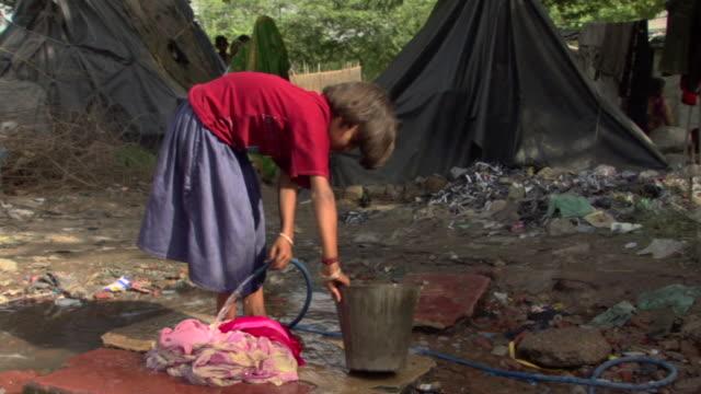 WS Woman in shanty village washing clothes in bucket, Agra, Uttar Pradesh, India