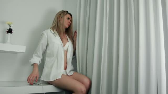 Frau in Hemd und Dessous, Blick aus dem Fenster