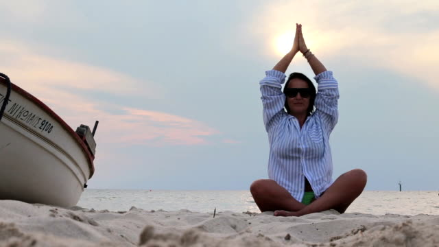 woman in shirt meditating on a beach near a sea and a boat - smart casual stock videos & royalty-free footage