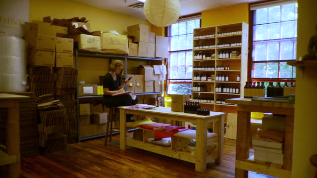 ws pan woman in shop taking inventory of her products / burlington, vermont, usa - burlington vermont stock videos & royalty-free footage