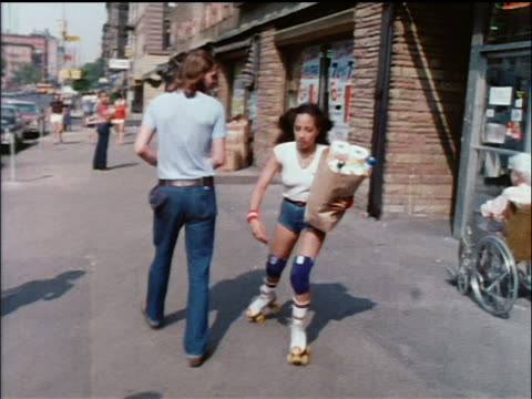 1978 woman in shorts carrying grocery bag roller skating out of grocery store onto nyc sidewalk - 1978 stock videos and b-roll footage