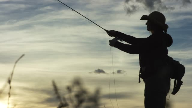 a woman in silhouette fly fishes at sunset under a partly cloudy sky - fly fishing stock videos and b-roll footage