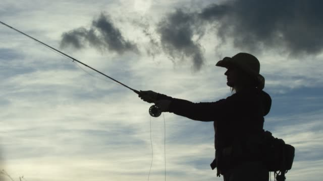 a woman in silhouette fly fishes at sunset under a partly cloudy sky - fishing rod stock videos & royalty-free footage