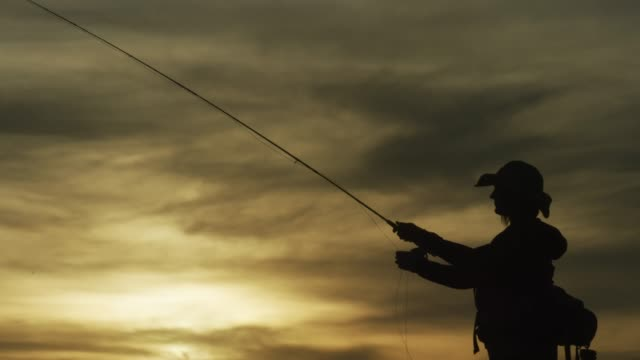 a woman in silhouette fly fishes at sunset under a partly cloudy sky - fishing stock videos & royalty-free footage