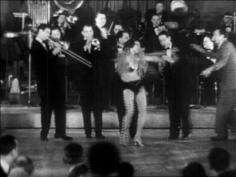 b/w 1928 woman in skimpy outfit dancing while big band plays in background / newsreel - 1920 stock-videos und b-roll-filmmaterial