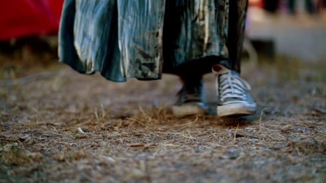 vídeos de stock, filmes e b-roll de mulher de saia andando em uma estrada suja - tênis calçados esportivos